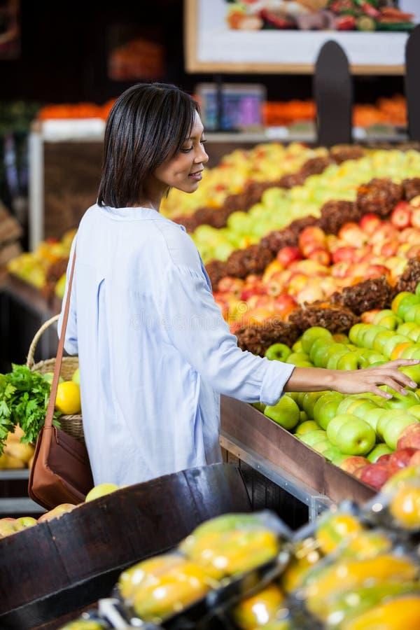 在有机部分的微笑的妇女买的果子 免版税库存照片