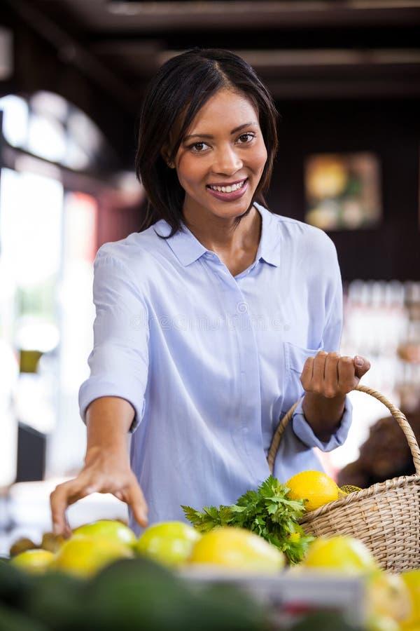 在有机部分的微笑的妇女买的果子 库存图片