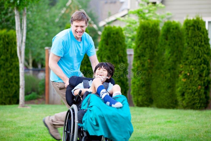在有残疾儿子的公园附近生赛跑轮椅的 库存图片