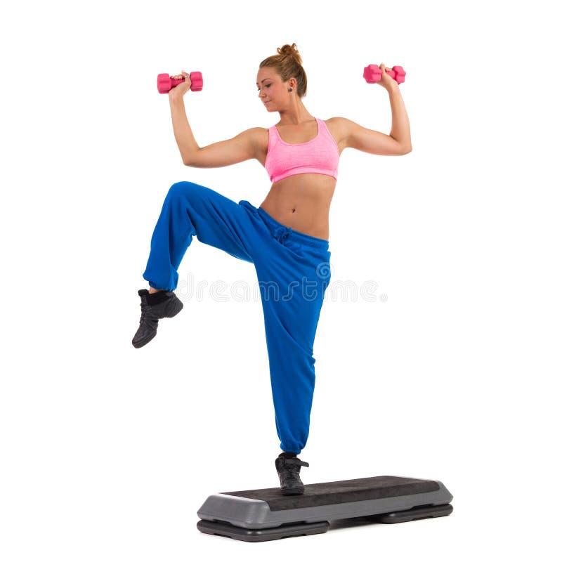 在有氧步的女性锻炼与手重量 免版税库存照片