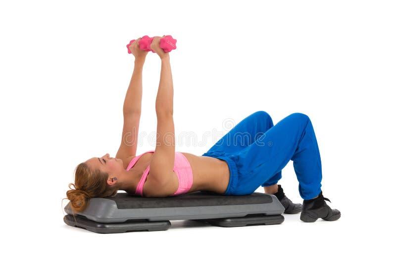 在有氧步的女性锻炼与手重量 免版税图库摄影