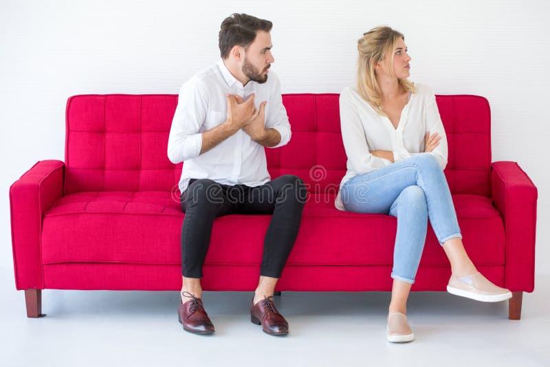 在有爱的女朋友和的男朋友的夫妇在红色沙发的争吵在家,户内 ?? 库存图片