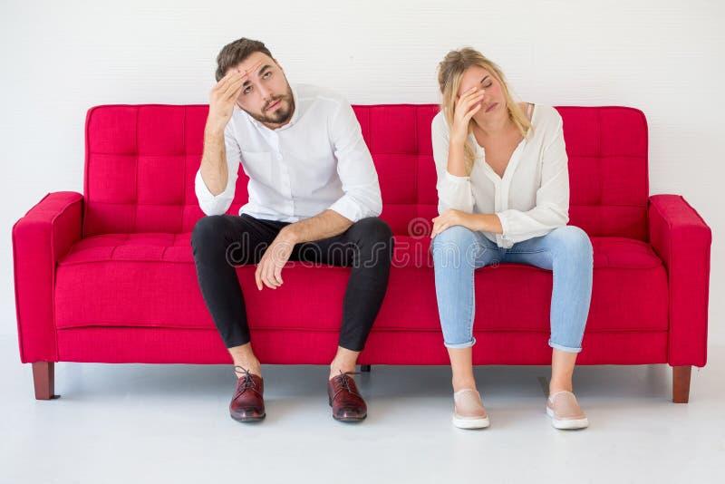 在有爱的女朋友和的男朋友的夫妇在红色沙发的争吵在家,户内 ?? 免版税库存图片