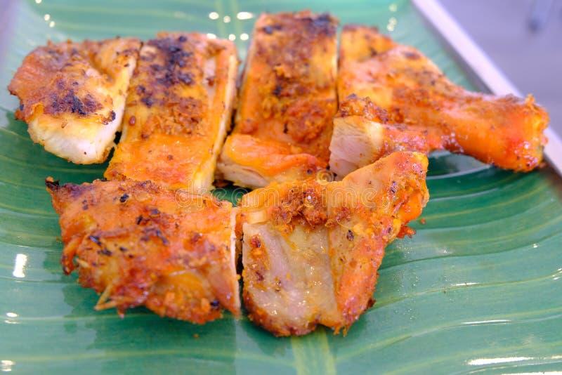 在有用卤汁泡的一块绿色板材安置的烤鸡用泰国样式调味汁 免版税库存照片