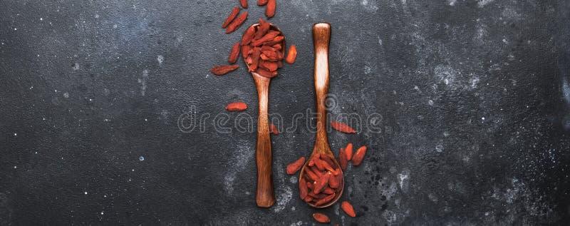 在有用灰色的背景-和健康食品概念,与地方的平的布局的干红色goji莓果文本的,横幅,顶视图 免版税图库摄影