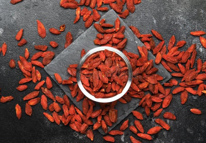 在有用灰色的背景-和健康食品概念,与地方的平的布局的干红色goji莓果文本的,顶视图 免版税库存图片