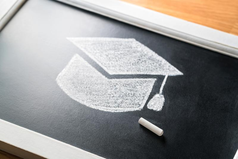 在有白垩的黑板画的毕业帽子 适用于学院或大学概念 传统教育 学习 免版税图库摄影