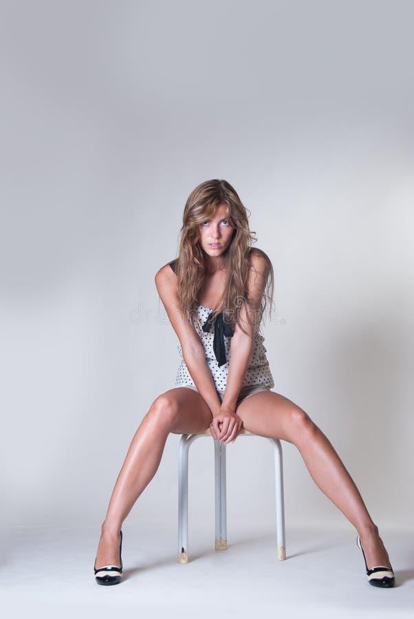 在有白皮书的演播室塑造有长的亭亭玉立的腿的妇女坐椅子 库存照片