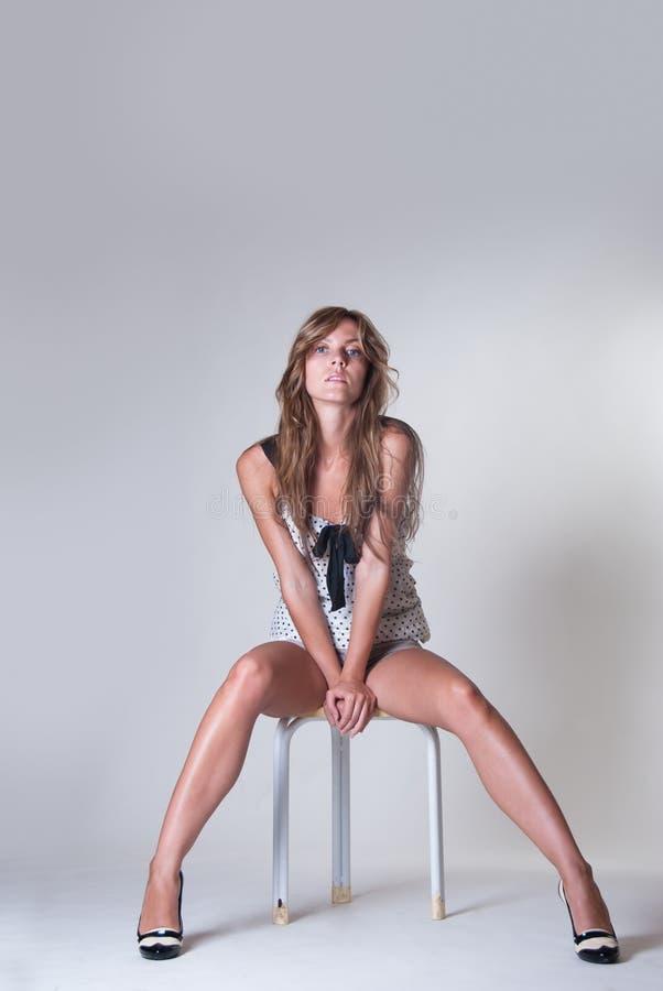 在有白皮书的演播室塑造有长的亭亭玉立的腿的妇女坐椅子 免版税图库摄影