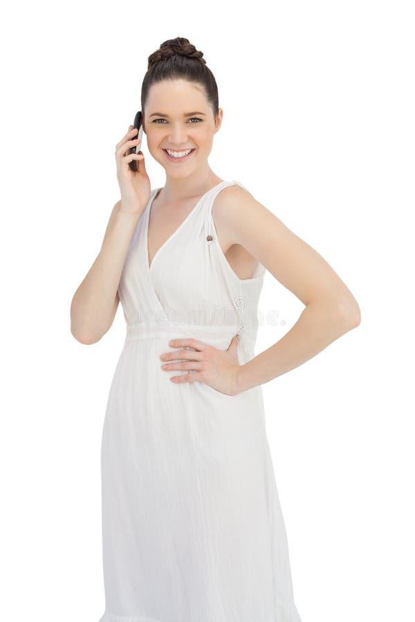 在有白色的礼服的快乐的年轻模型电话 库存照片