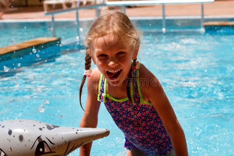 在有的水池的女孩游泳微笑和一愉快的天 免版税库存图片