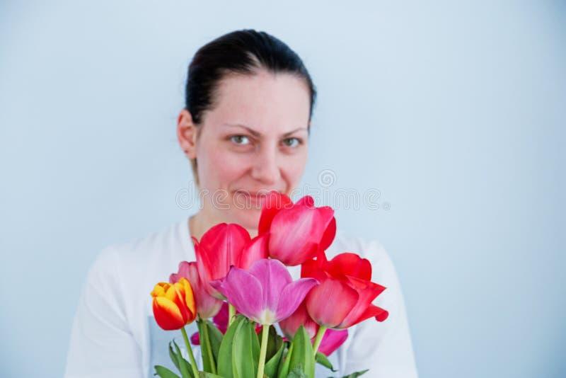 在有红色郁金香花束的焦点女孩外面在白色背景的 免版税库存照片
