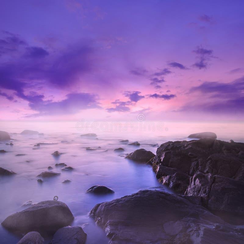 在有薄雾的岩石的桃红色和紫色日落在海 库存例证
