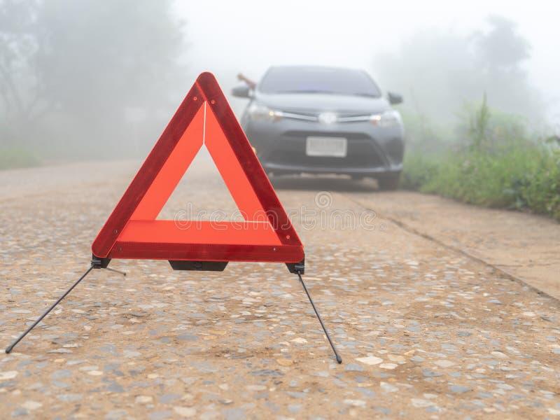 在有薄雾的有雾的路的一次汽车故障 司机要求紧急帮助 在路,交通警告的三角的人汽车残破的麻烦 库存图片