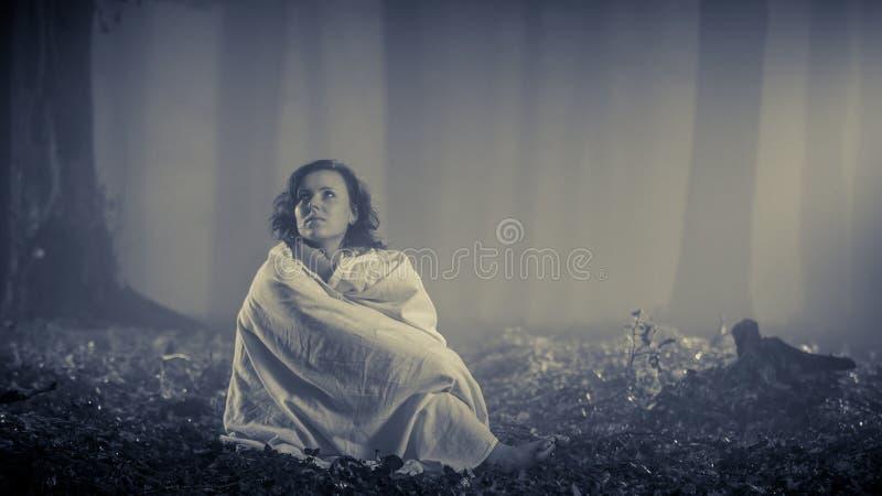 在有薄雾的森林里寻找帮助的失去的妇女 免版税图库摄影