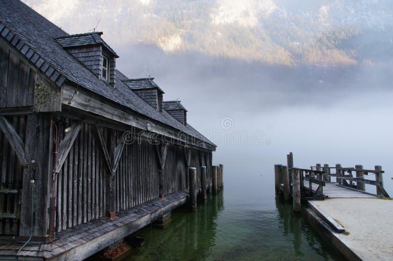 在有薄雾的湖Konigssee旁边的船库 免版税库存图片