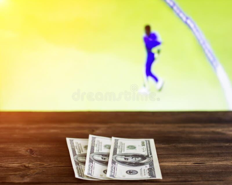 在有蟋蟀,体育打赌,蟋蟀体育比赛电视的背景的金钱美元 免版税库存图片