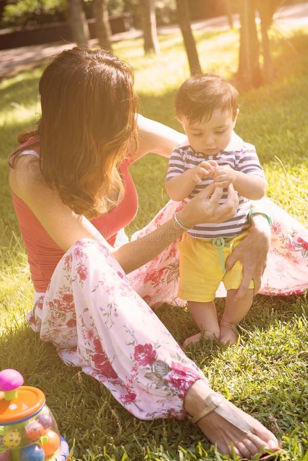 在有被应用的温暖的过滤器的公园照顾与她的儿子的戏剧 图库摄影