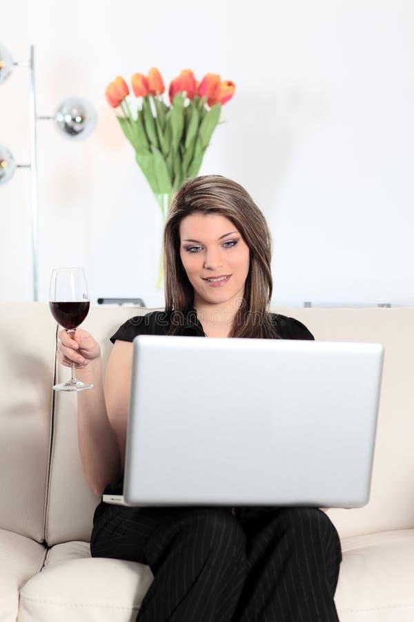 在有计算机和酒杯的沙发上 库存照片