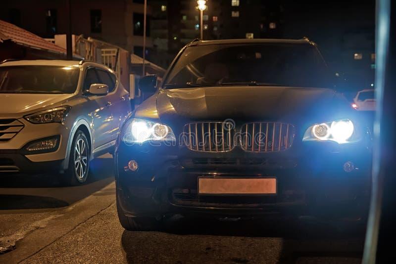 在有雾的汽车车灯 晚上夜时间 在城市道路的汽车 晚上夜间 在晚上汽车烧毁 免版税库存照片