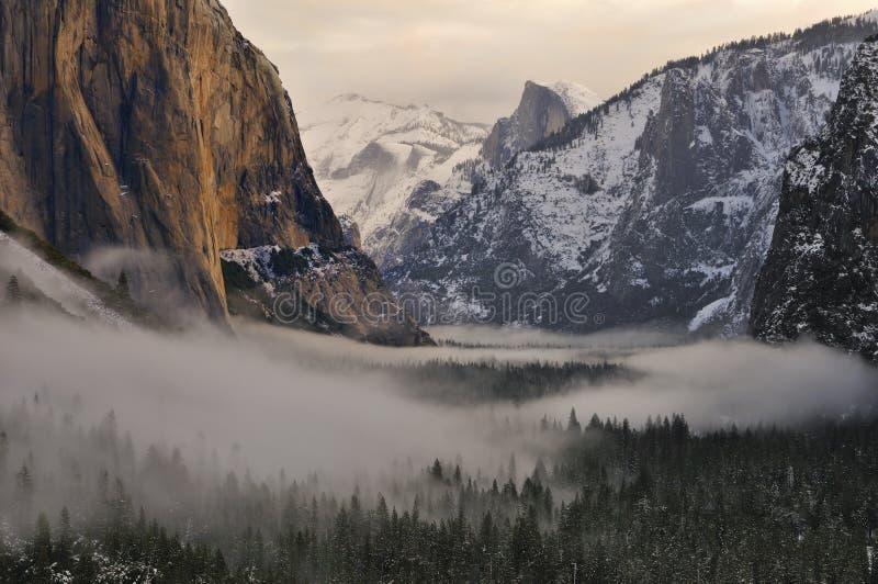 在有雾的谷,优胜美地国家公园的El Capitan和半圆顶 免版税库存照片