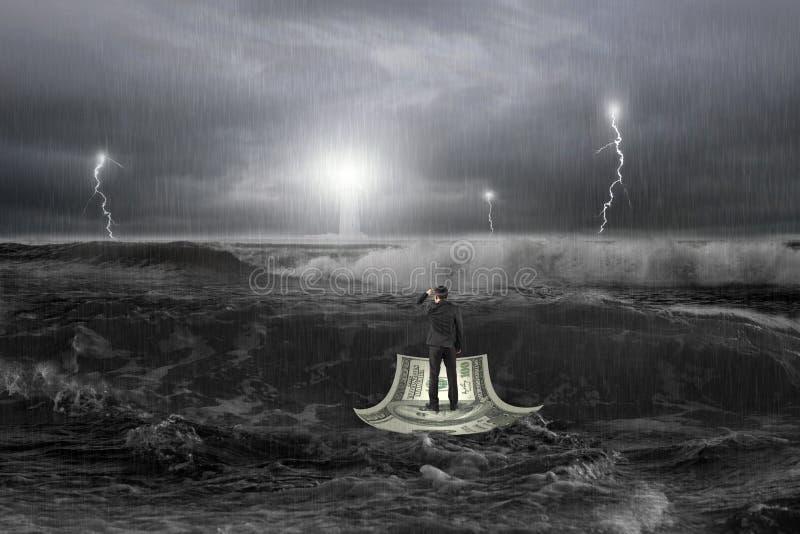 在有风暴的海洋供以人员注视在金钱小船的灯塔 免版税库存图片