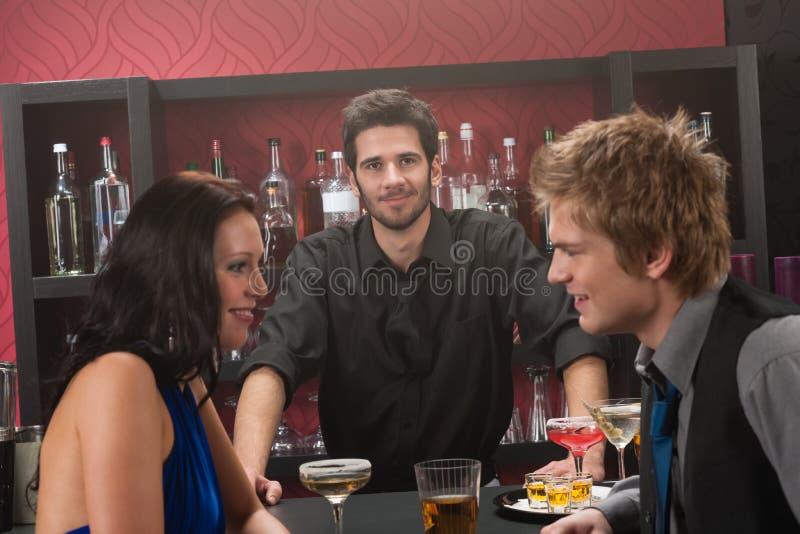 在有饮料的朋友之后的棒酒吧招待 免版税库存照片
