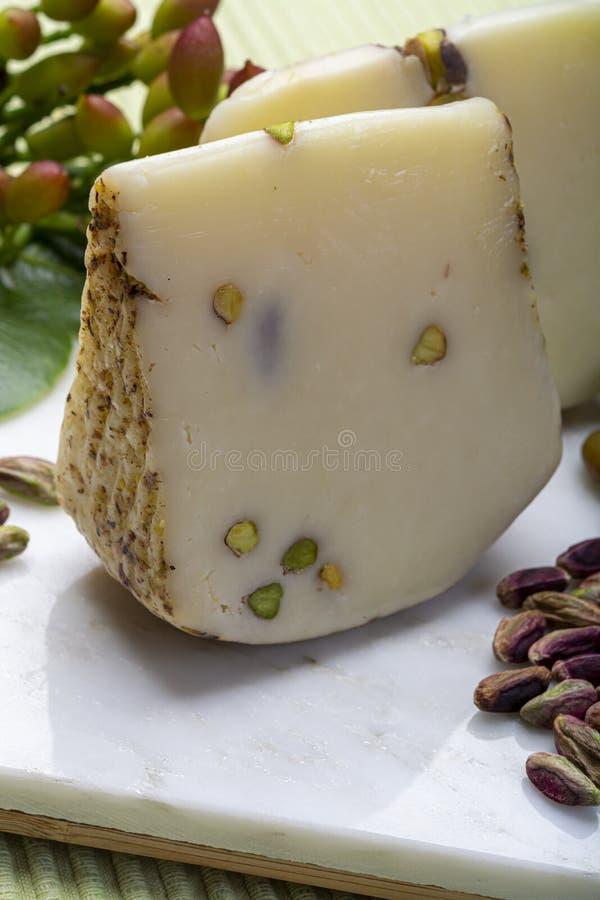 在有鲜美绿色布龙泰开心果的西西里岛制造的意大利普罗卧干酪或provola乳酪在白色大理石板材关闭服务  免版税库存图片