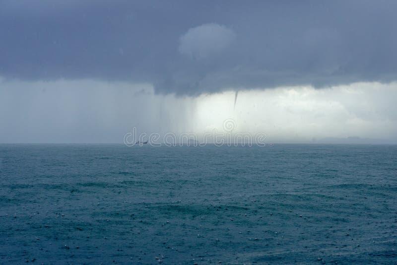 在有黑暗的云彩和龙卷风的海下雨 库存图片