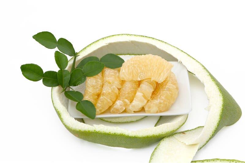 在有绿色叶子和果皮的一块白色板材上把放的柚在白色 图库摄影