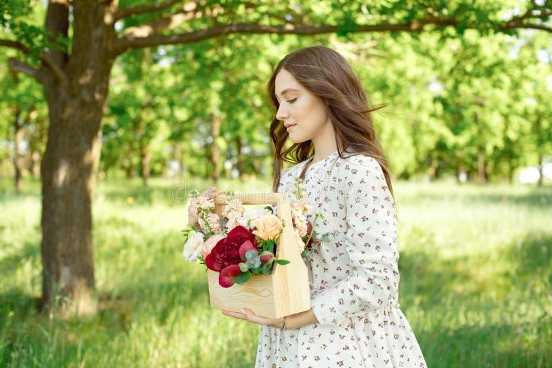 在有a的长的白色夏天礼服打扮的一名迷人的正面妇女的半画象幸福微笑在绿色的背景 免版税库存图片