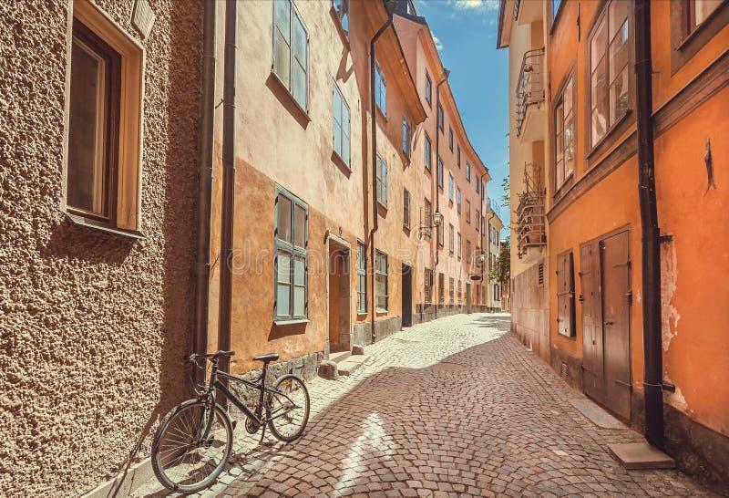 在有Gamla斯坦老镇老房子的狭窄的五颜六色的街道上放弃的自行车在Sockholm,瑞典 免版税库存图片