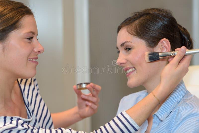 在朋友的化妆师工作 免版税库存图片