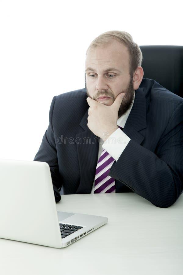 在服务台上的商人认为后边膝上型计算机 免版税库存照片