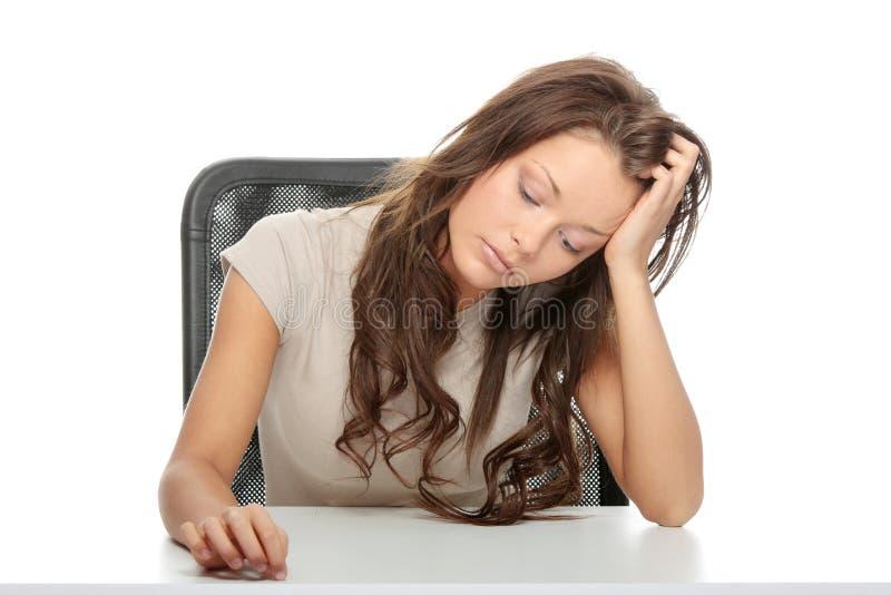 在服务台哀伤的坐的妇女之后 库存图片