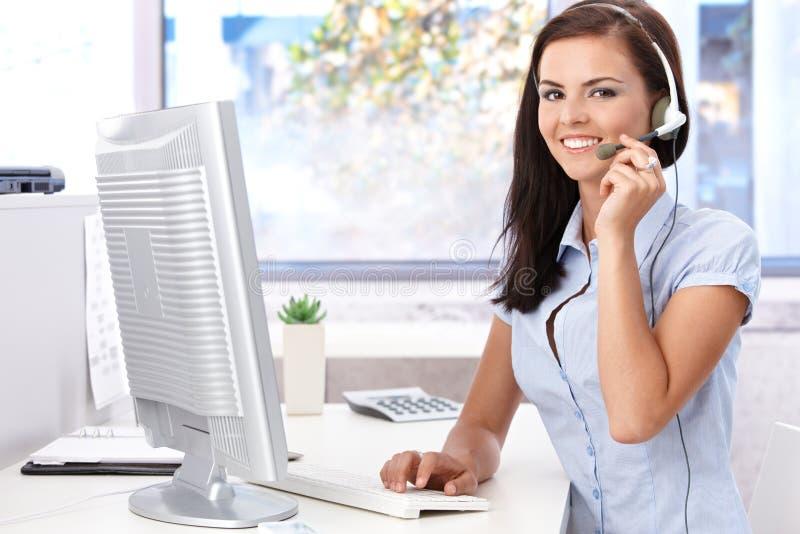 在服务台的愉快的女性开会在明亮的办公室 库存图片