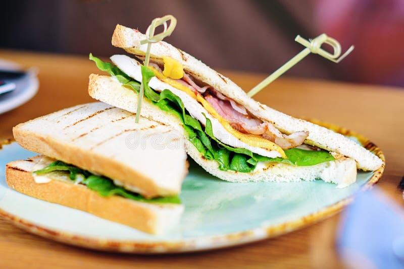 在服务的板材的火腿、乳酪、沙拉和烤面包片三明治 库存图片