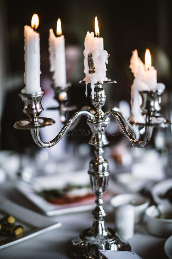 在服务的表上的典雅的古色古香的烛台 免版税库存照片