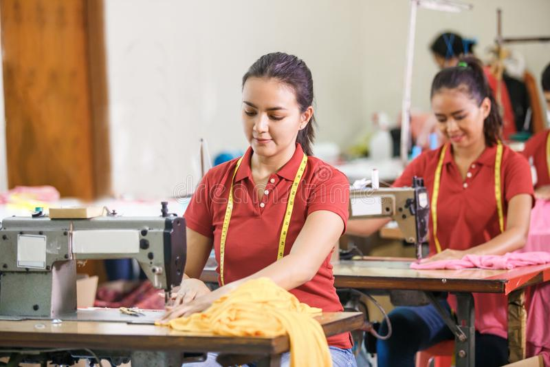 在服装工厂缝合与工业sewin的亚裔裁缝 免版税库存照片