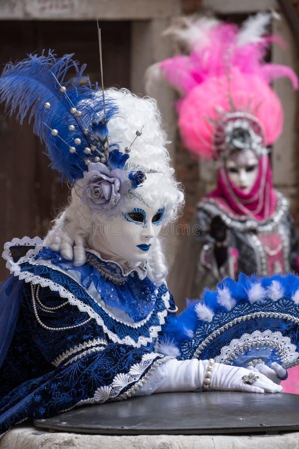在服装的两个面具有爱好者的和在威尼斯狂欢节的华丽被绘的用羽毛装饰的面具 免版税库存照片