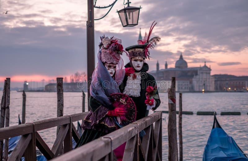 在服装的夫妇和面具站立与回到大运河的,圣乔治在背景中,在威尼斯狂欢节期间 库存图片