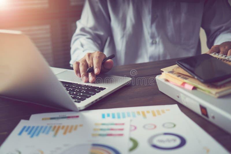 在木书桌上的商人手运转的膝上型计算机在早晨光的办公室 现代的概念与先进技术一起使用 免版税库存照片