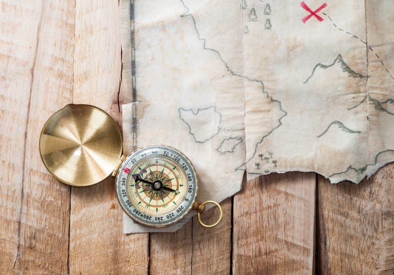 在木书桌上的指南针有伪造品的盗版与红旗十字架的珍宝老地图 库存照片