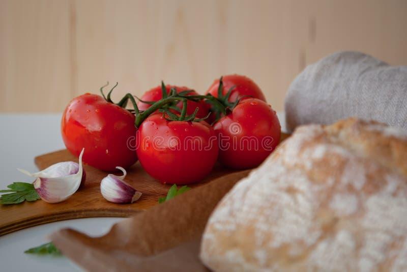 在木书桌上的新鲜的蕃茄用大蒜 库存照片