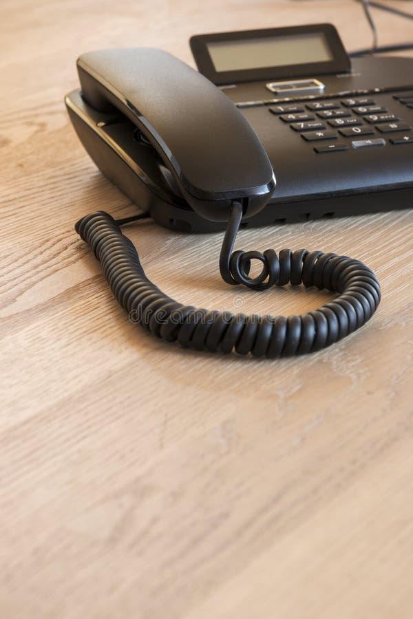 在木书桌上的现代黑电话 免版税库存图片