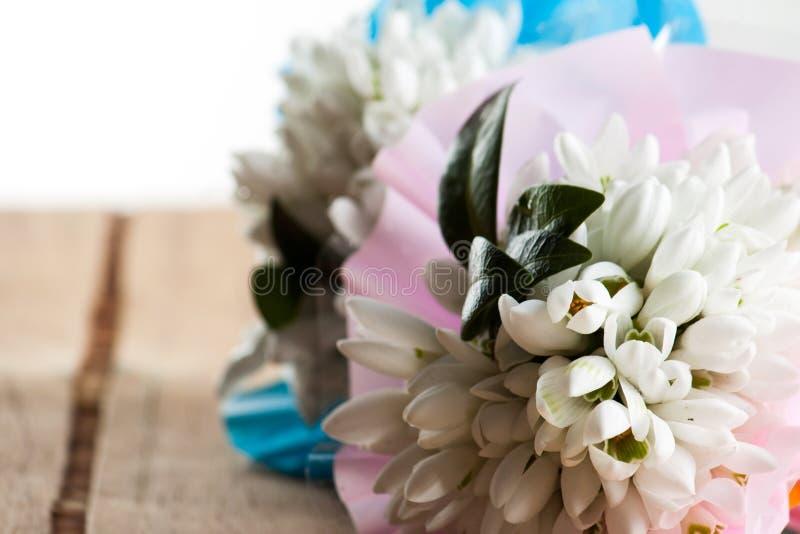 在木书桌上的白色花束snowdrops 免版税图库摄影