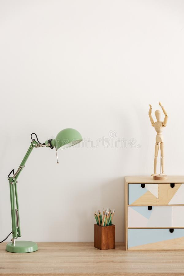 在木书桌有书的,在空的白色墙壁上的拷贝空间的淡色薄荷的色的灯 免版税库存照片