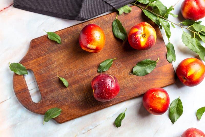 在木修整器的新鲜的油桃在大理石桌上 库存照片