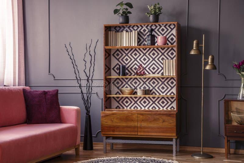 在木内阁和金灯旁边的桃红色沙发在灰色生活ro 免版税库存图片