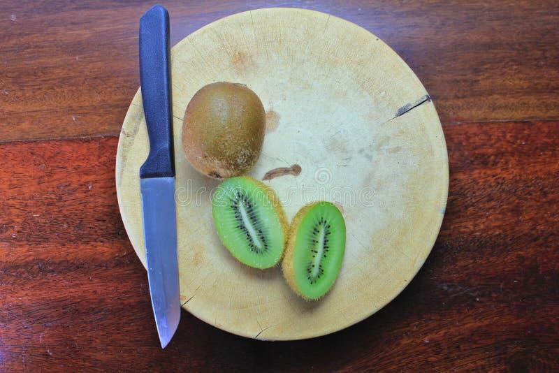 在木切板刀子的新鲜的猕猴桃在果子表上 库存图片